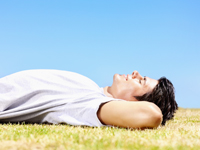 man-laying-in-grass-health-wellness