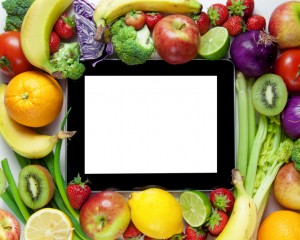 Fruits and vegetables around a computer tablet with an empty screen copy space